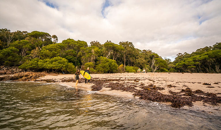 People walking along the beach at Bittangabee Bay in Ben Boyd National Park. Photo: John Spencer/OEH