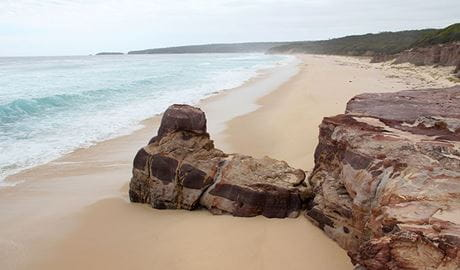 View down Long Beach showing rock formations, dunes, cliffs and coastal bushland. Photo: John Yurasek © DPIE