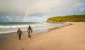 Surfers on the beach at Saltwater Creek campground, Ben Boyd National Park. Photo: J Spencer/OEH