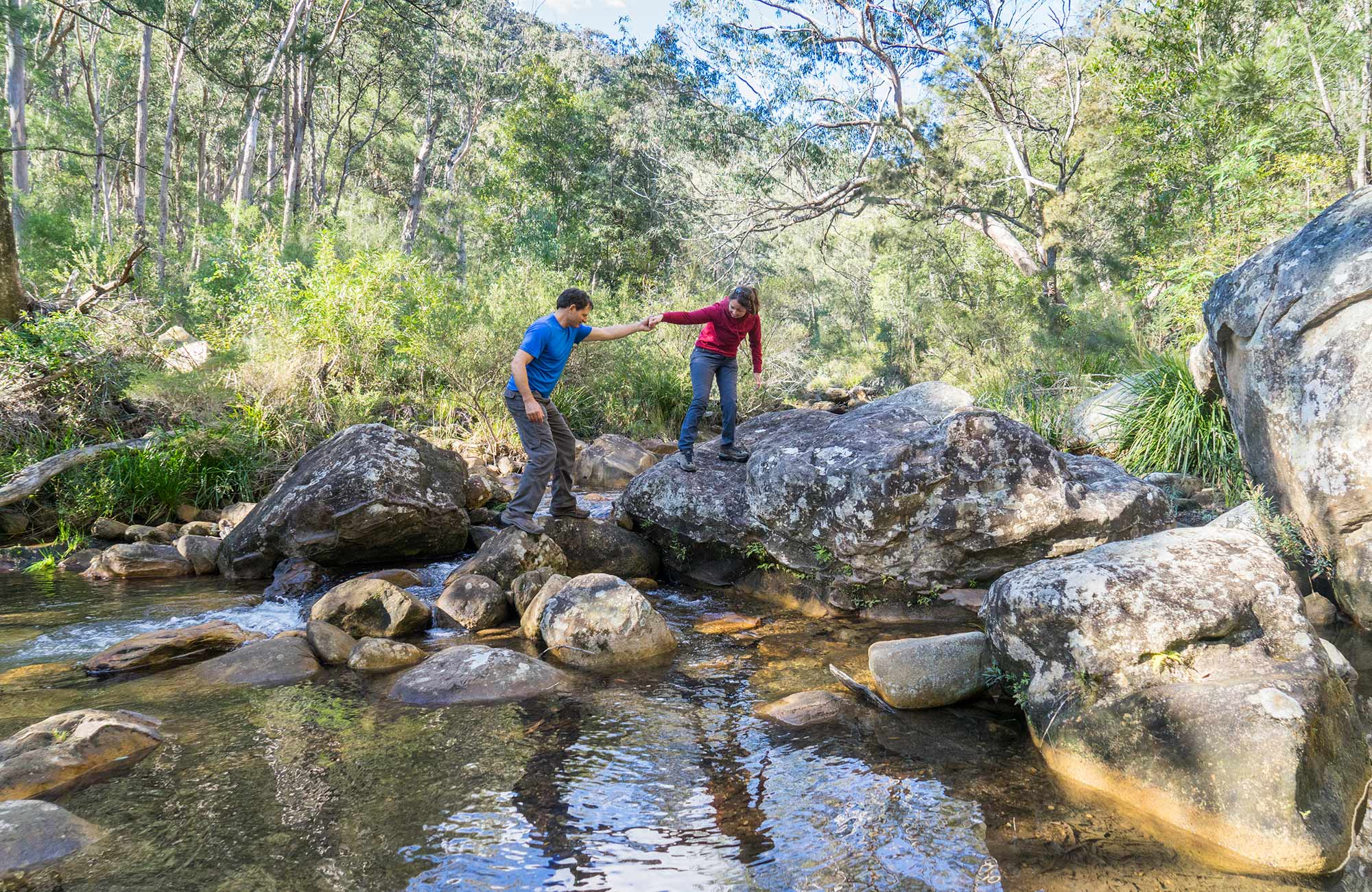 Hikers rock hopping on Rodriguez Pass walking track, Blue Mountains National Park. Photo: Simone Cottrell/OEH.