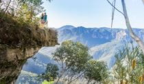 Walkers looking out at views from Breakfast Rock,  Govetts Leap descent walk. Photo: OEH/Simone Cottrell