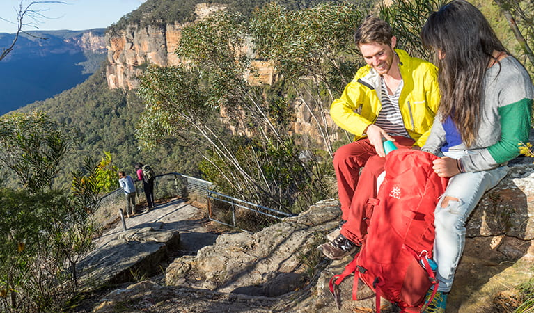 Walkers with a day pack sitting on Breakfast Rock along Govetts Leap descent. Photo: OEH/Simone Cottrell