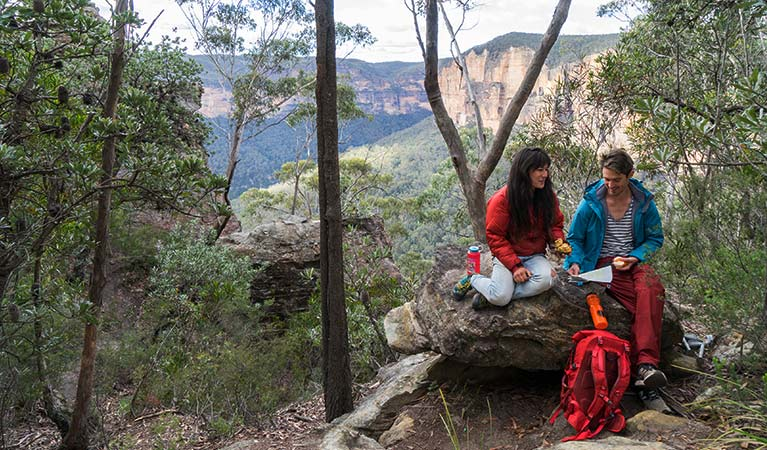 A couple sit on a rock near start of Grand Canyon track, Blue Mountains National Park. Photo: Simone Cottrell/OEH.