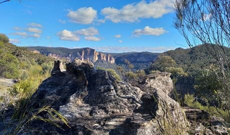 Rocky outcrop with a wide vista of cliffs and mountains cloaked in forest. Photo: Dave Noble/DPIE