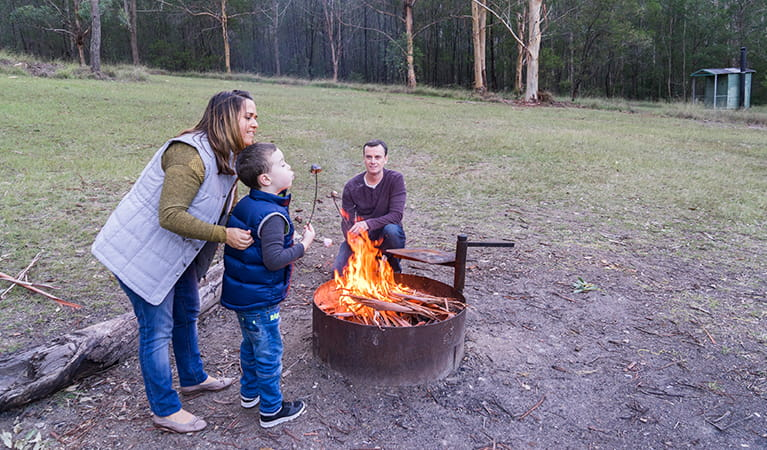 Family roast marshmellows by a fire in the Nikoa section of Euroka campground. Photo: OEH/Simone Cottrell