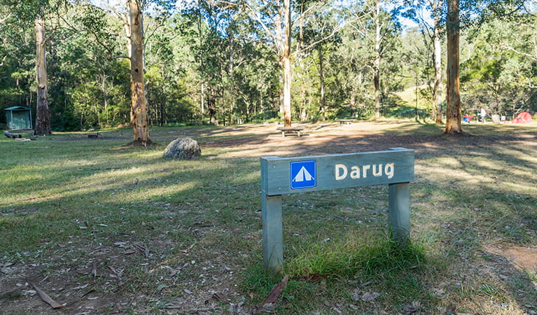 Signpost showing the Darug section of Euroka campground with toilets in the background. Photo: OEH/Simone Cottrell