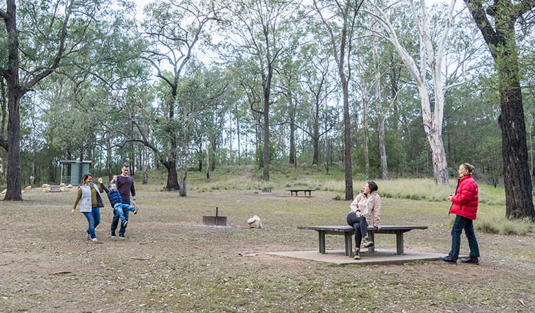 Family enjoy a walk around the Bennett Ridge section of Euroka campground with toilets in the background. Photo: OEH/Simone Cottrell