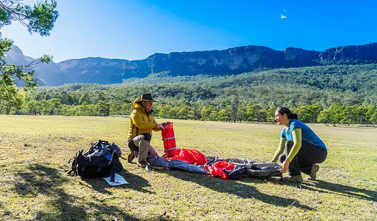 A couple set up a tent at Kedumba River Crossing campground, Blue Mountains National Park. Photo: Simone Cottrell/OEH