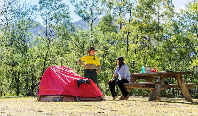 A camper and a ranger sit at a picnic table beside a tent, Kedumba River Crossing campground, Blue Mountains National Park. Photo: Simone Cottrell/OEH