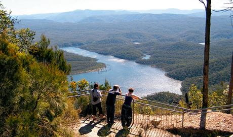 Three people at McMahons Point lookout above Lake Burragorang, Blue Mountains National Park. Photo: Craig Marshall/OEH
