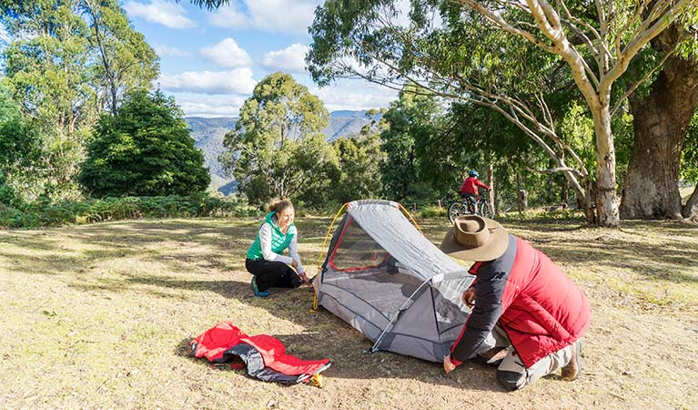 A couple pitch a tent at Dunphys campground, Blue Mountains National Park. Photo: Simone Cottrell/OEH.