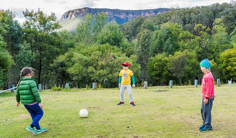 Three kids play soccer at Dunphys campground, Blue Mountains National Park. Photo: Simone Cottrell/OEH.