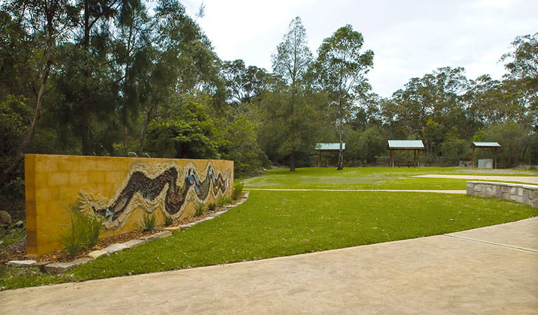Community art mural at the entrance to Bomaderry Creek Regional Park with picnic shelters in the background. Photo: Michael Van Ewijk © DPIE