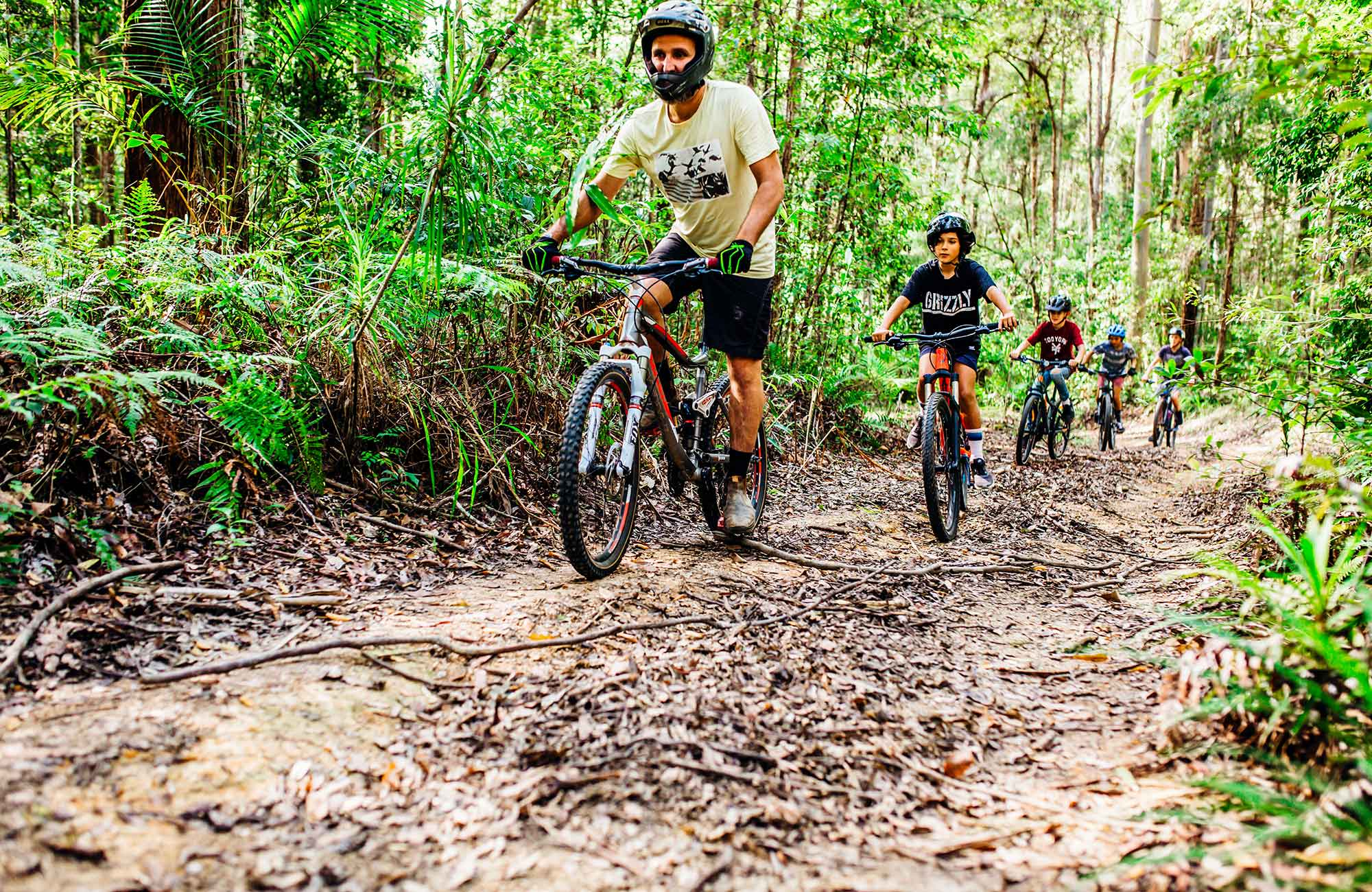A man and 4 children ride along a forest track, part of the Muurlay Baamgala cycle trails in Bongil Bongil National Park. Photo: Jay Black/DPIE