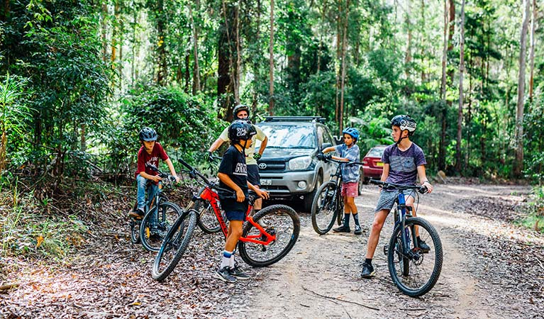 A man and 4 children with mountain bikes stand next to vehicles on one of the Muurlay Baamgala cycle trails. Photo: Jay Black/DPIE