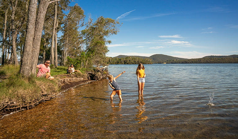 A family plays on the shore of Wallis Lake, in Booti Booti National Park. Photo credit: John Spencer & copy; DPIE