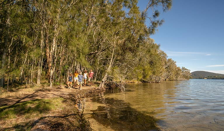 A group walks along a path beside Wallis Lake, near The Ruins campground in Booti Booti National Park. Photo credit: John Spencer & copy; DPIE