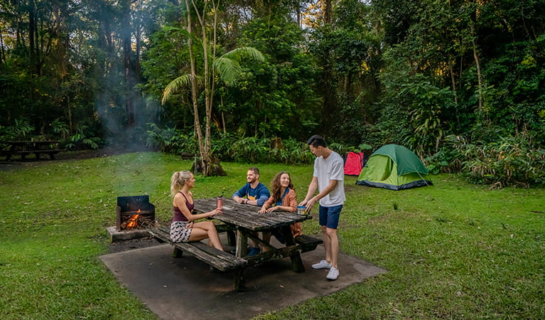 Friends camping and cooking by the fire at Sheepstation Creek campground. Photo: DPIE/ John Spencer