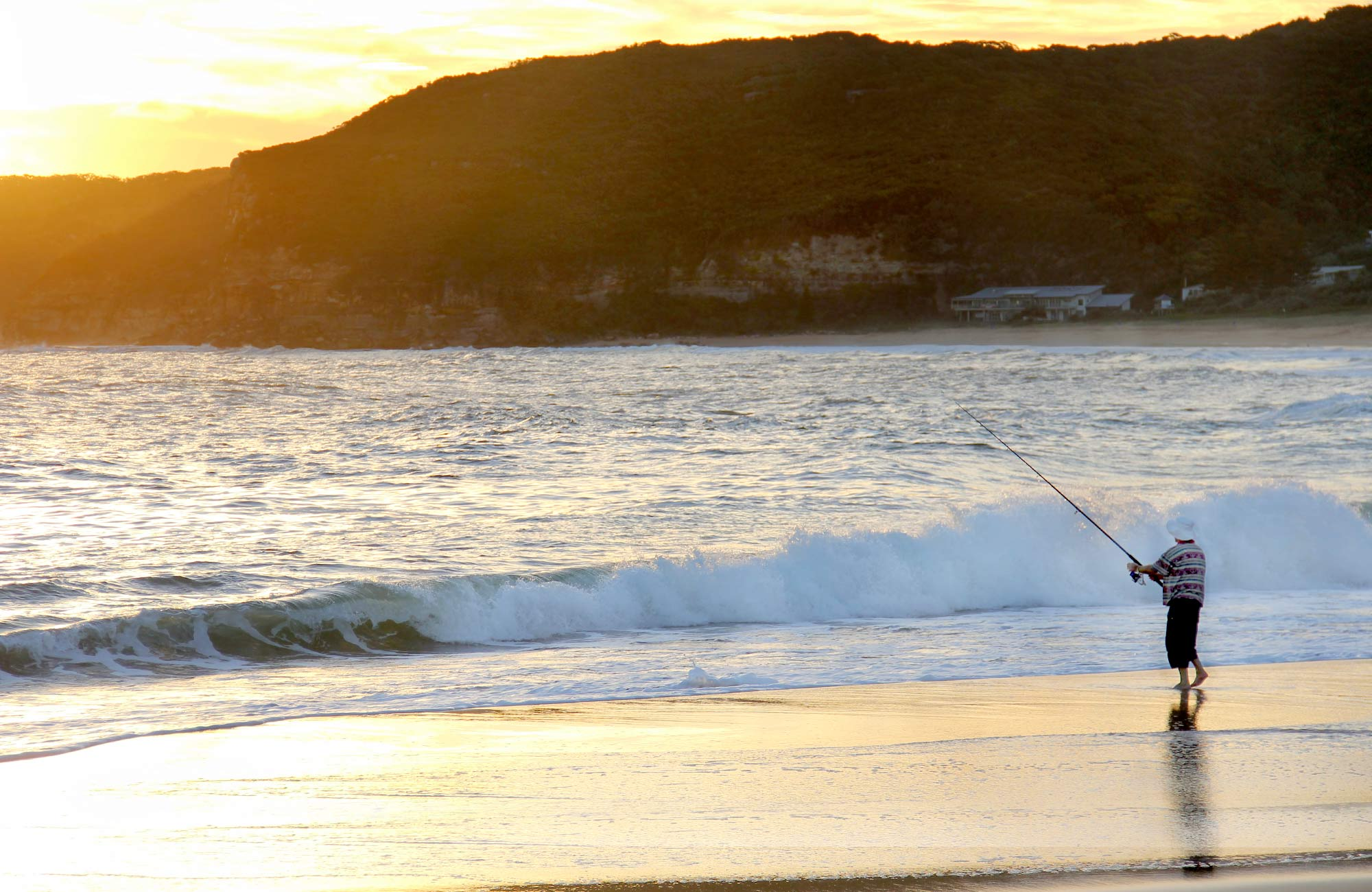 A person fishing on the beach and sunrise. Photo: John Yurasek