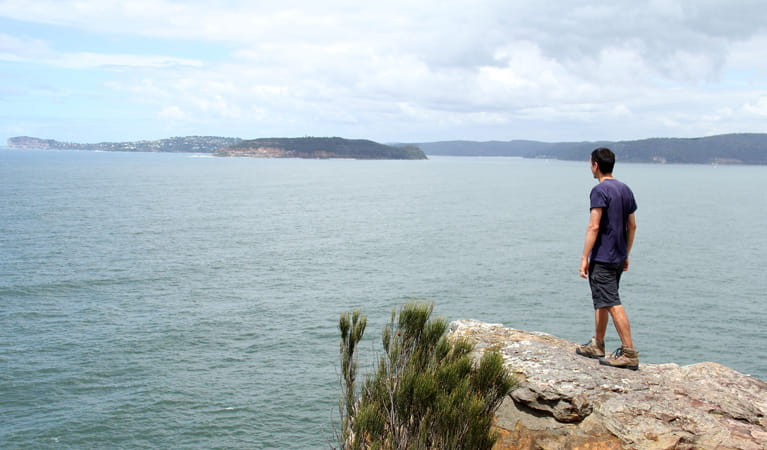 Man looks out at the water from a rock. Photo: John Yurasek
