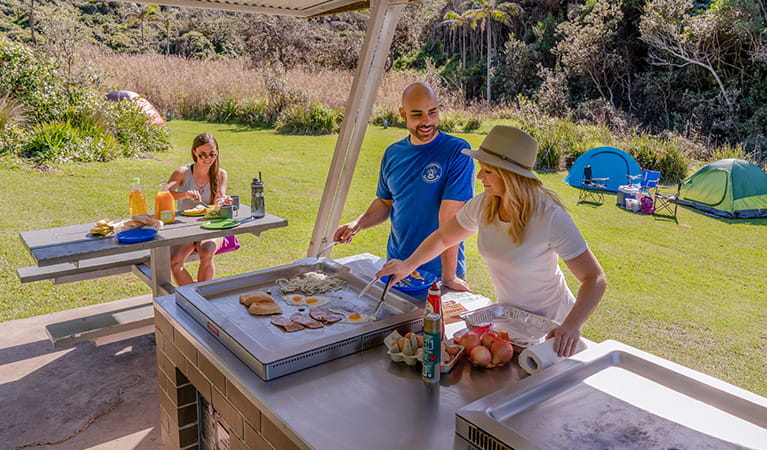 Campers under the barbecue shelter cooking and enjoying breakfast, Bouddi National Park. Photo: John Spencer/DPIE.