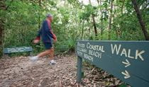 A man walks past directional park signs in Bouddi National Park. Photo credit: Nick Cubbin. <HTML>&copy; OEH