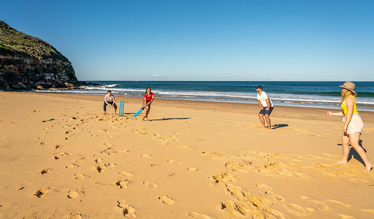 People playing a game of cricket along Tallow Beach, Bouddi National Park. Photo: John Spencer/DPIE.