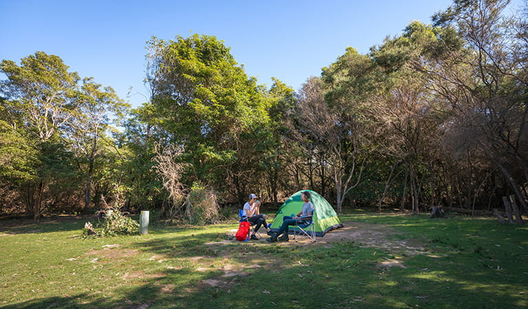 Two campers sitting outside their tent at Hobart Beach campground, Bournda National Park. Photo: Daniel Tran/DPIE