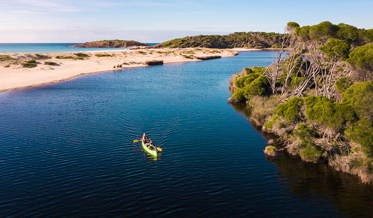 Two people in a canoe on Bournda Lagoon, Bournda National Park. Photo: Daniel Tran/DPIE