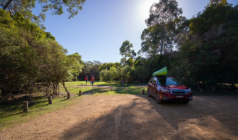 Two people walking away from a car parked at Hobart Beach campground, Bournda National Park. Photo: Daniel Tran/DPIE