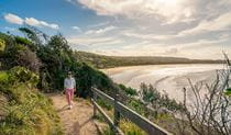 A woman walking along Three Sisters walking track, overlooking the beach in Broken Head Nature Reserve. Photo: John Spencer/DPIE