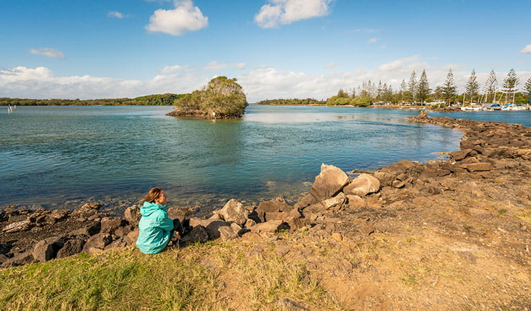 A woman sitting by the water at Brunswick River picnic area in Brunswick Heads Nature Reserve. Photo: John Spencer/DPIE