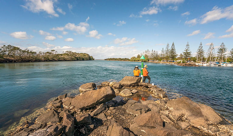 2 people fishing on the rocks at Brunswick River picnic area in Brunswick Heads Nature Reserve. Photo: John Spencer/DPIE