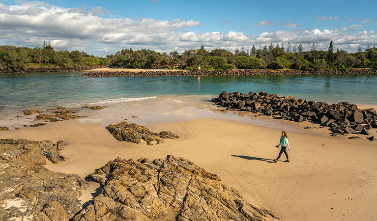 Woman walking along the beach at North Head walking track in Brunswick Heads Nature Reserve. Photo: John Spencer/DPIE