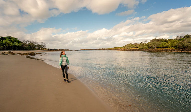 A woman walking along the beach at North Head walking track in Brunswick Heads Nature Reserve. Photo: John Spencer/DPIE