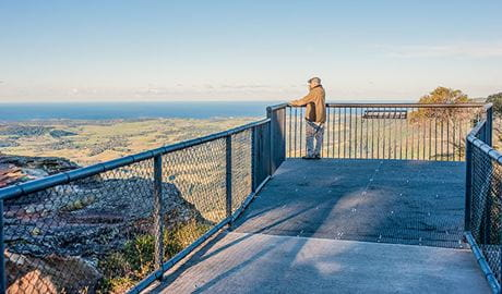 A man stands at Jamberoo lookout, Budderoo National Park. Photo credit: Michael Van Ewijk © DPIE