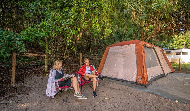 A couple relax, reading magazines beside their tent at Woody Head campground, Bundjalung National Park. Photo: John Spencer/OEH