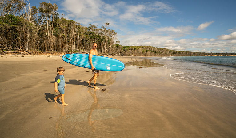 A father and young son head down to the water for a paddle, Woody Head campground, Bundjalung National Park. Photo: John Spencer/OEH