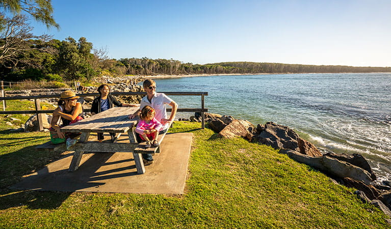 A group at a picnic table by the water, Woody Head campground, Bundjalung National Park. Photo: John Spencer/OEH