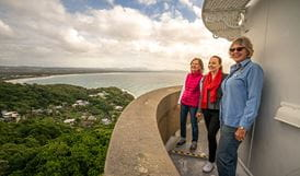 Three women enjoy views from the top of Cape Byron Lighthouse, Cape Byron State Conservation Area. Photo: John Spencer/OEH.