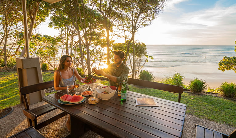 Couple eating outdoors at sunset with views of the beach from Mildenhall Cottage. Photo: John Spencer © DPIE