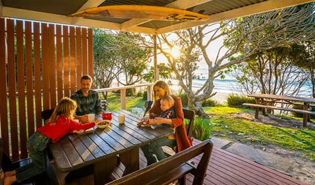 Family on the back deck of Partridge cottage overlooking Byron Bay beach. Photo: DPIE/John Spencer