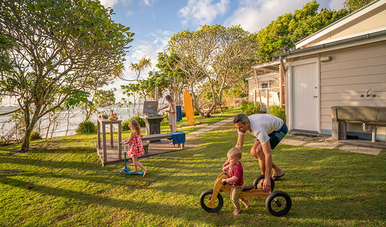 Family in the garden overlooking Byron Bay beach from Partridge Cottage. Photo: DPIE/John Spencer