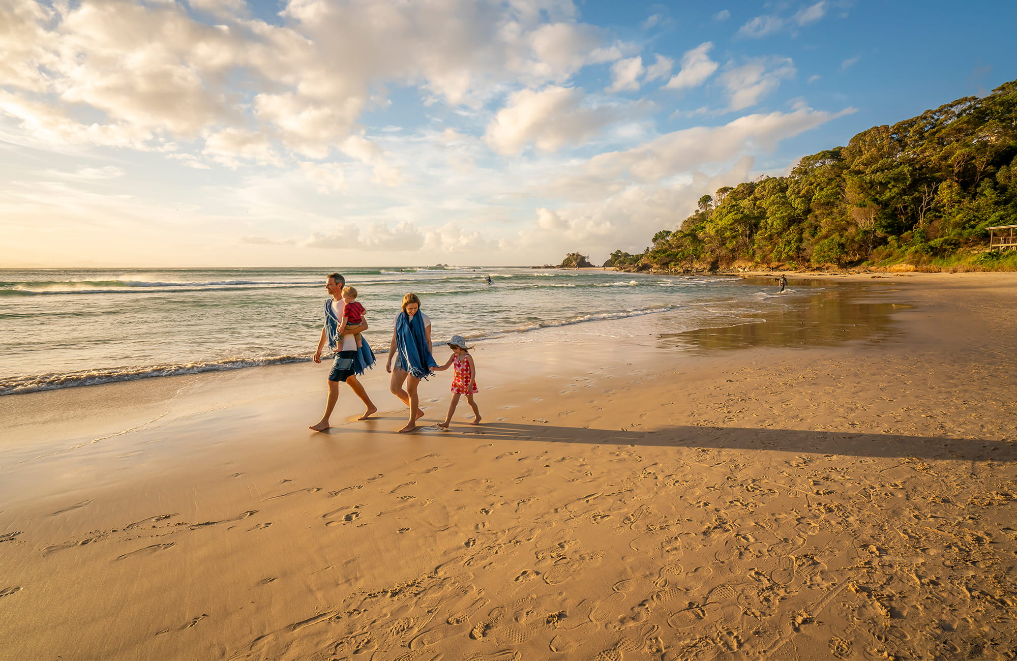Family walking Byron Bay beach. Photo: DPIE/John Spencer