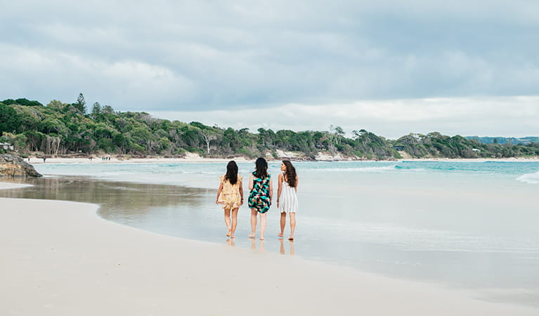 3 friends walking on The Pass beach in Cape Byron State Conservation Area. Photo: Sera Wright/DPIE