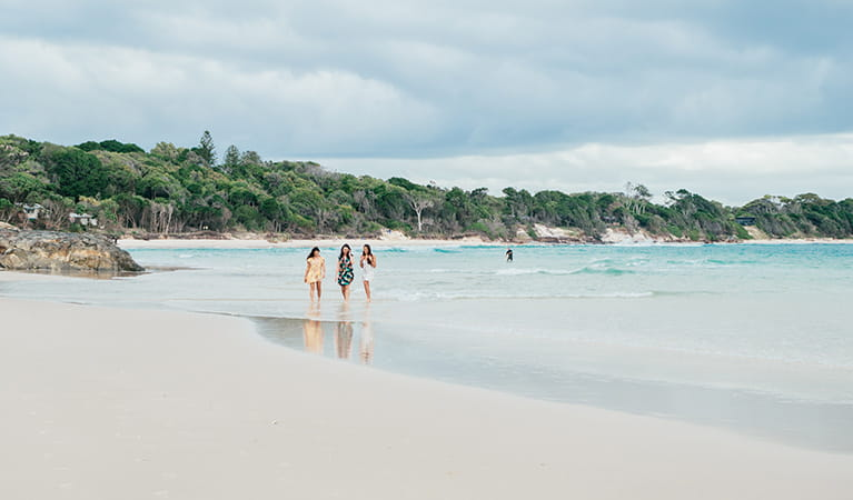 3 friends walking on the beach near Thomson Cottage. Photo: Sera Wright © DPIE