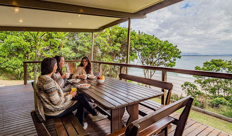Friends having breakfast with ocean views on the verandah of Thomson Cottage. Photo: Sera Wright © DPIE