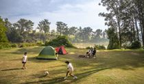 Parents sit outside their tent beside the Hawkesbury River while their kids play soccer, at Cattai campground in Cattai National Park. Photo: John Spencer/OEH