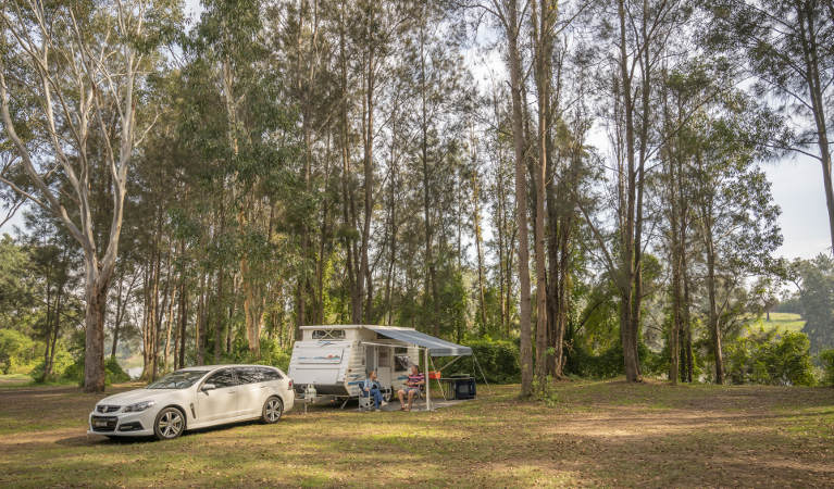 A couple sit outside their caravan at Cattai campground in Cattai National Park, on the Hawkesbury River. Photo: John Spencer/OEH