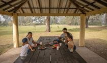 A family enjoys a barbecue lunch in a picnic shed at Cattai Farm picnic area in Cattai National Park, on the Hawkesbury River. Photo: John Spencer/OEH